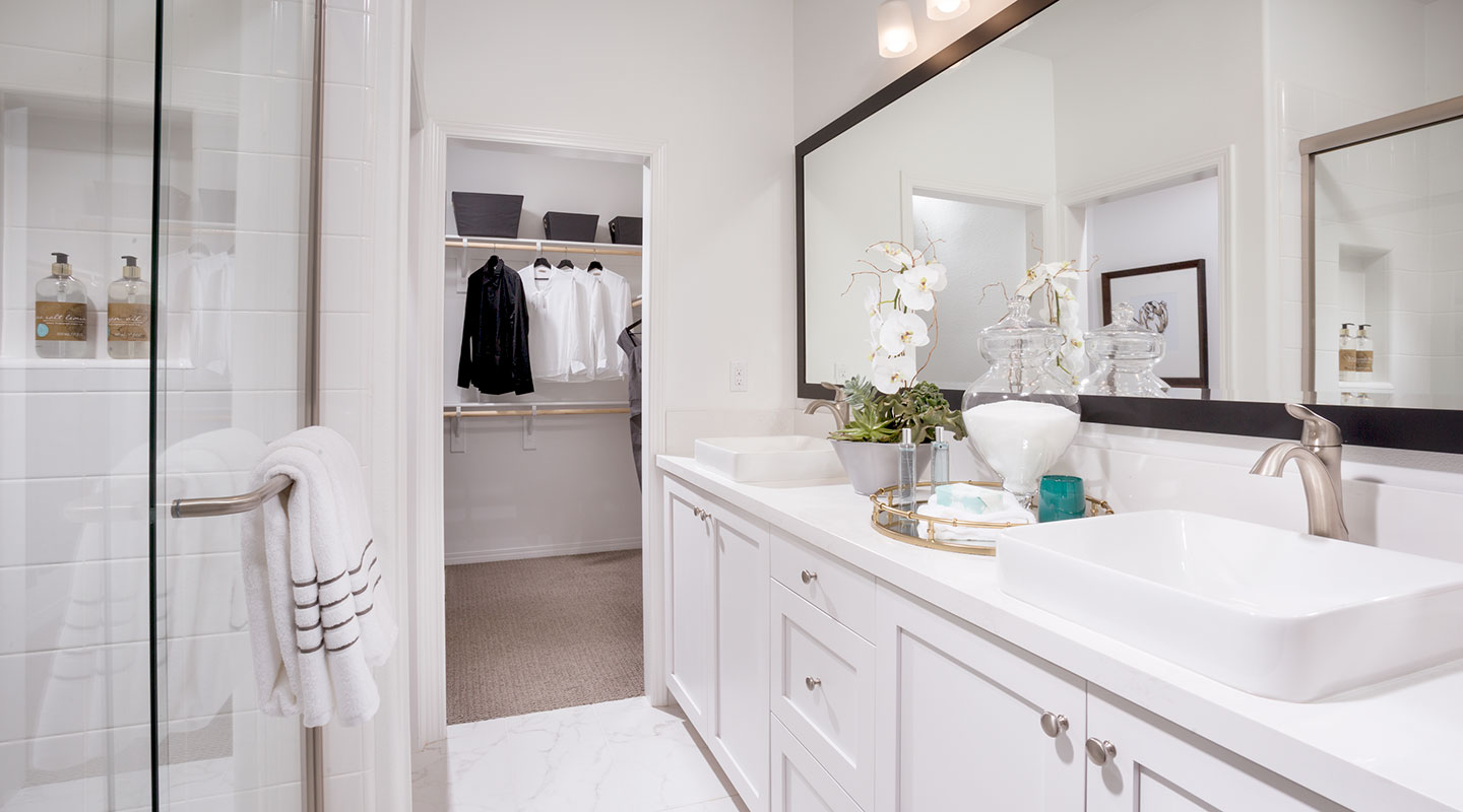 Los Alamitos Townhome Interior bathroom with walk in closet and double vanity sinks